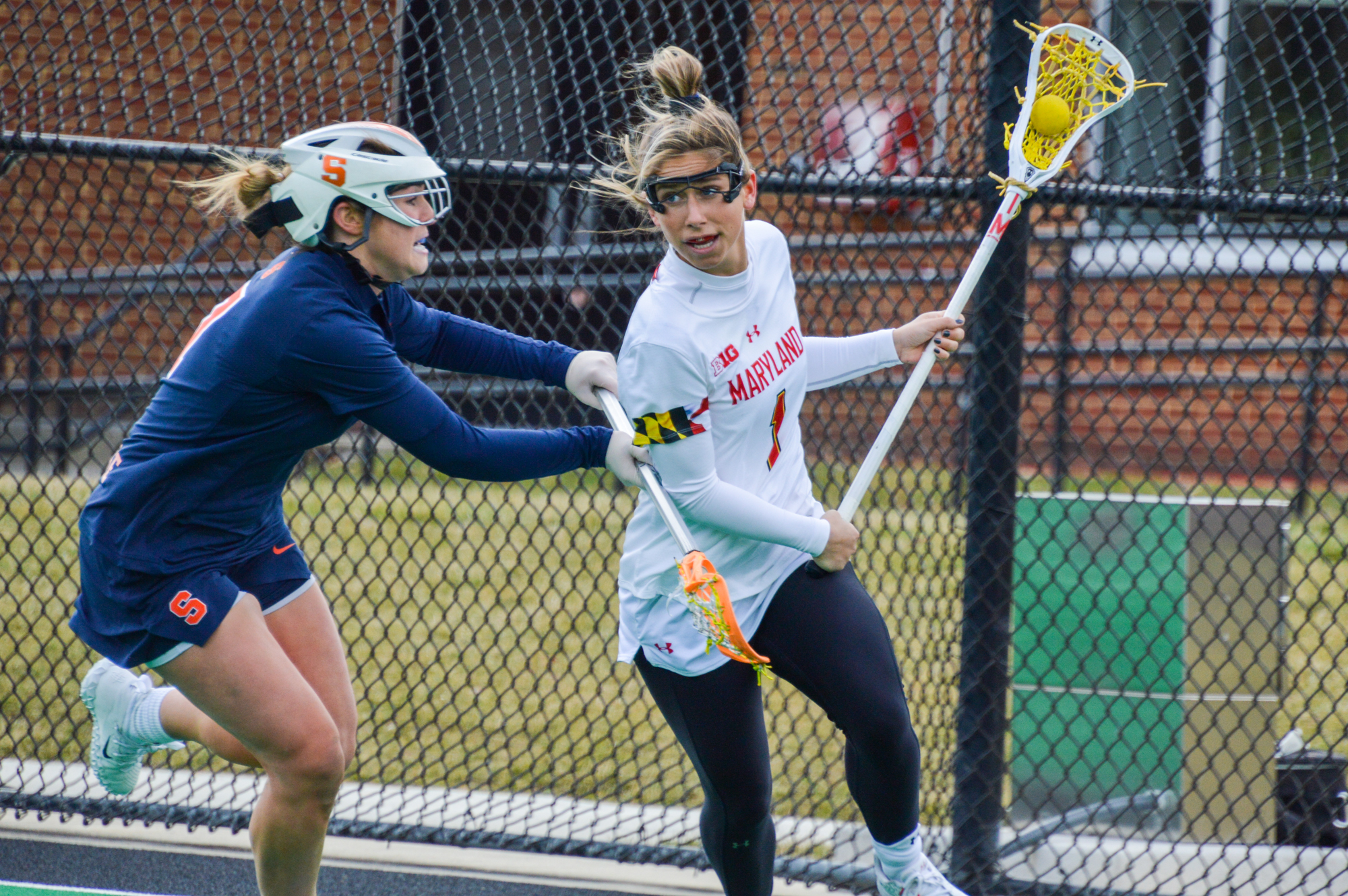 Woman in a white jersey with a lacrosse stick and ball running past a woman in a blue jersey with a lacrosse stick