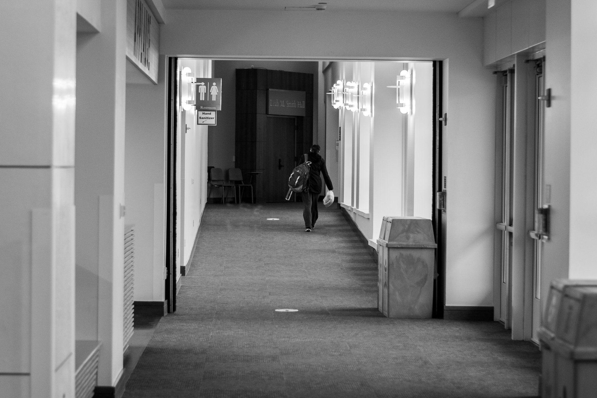 A person walks through an otherwise empty hallway