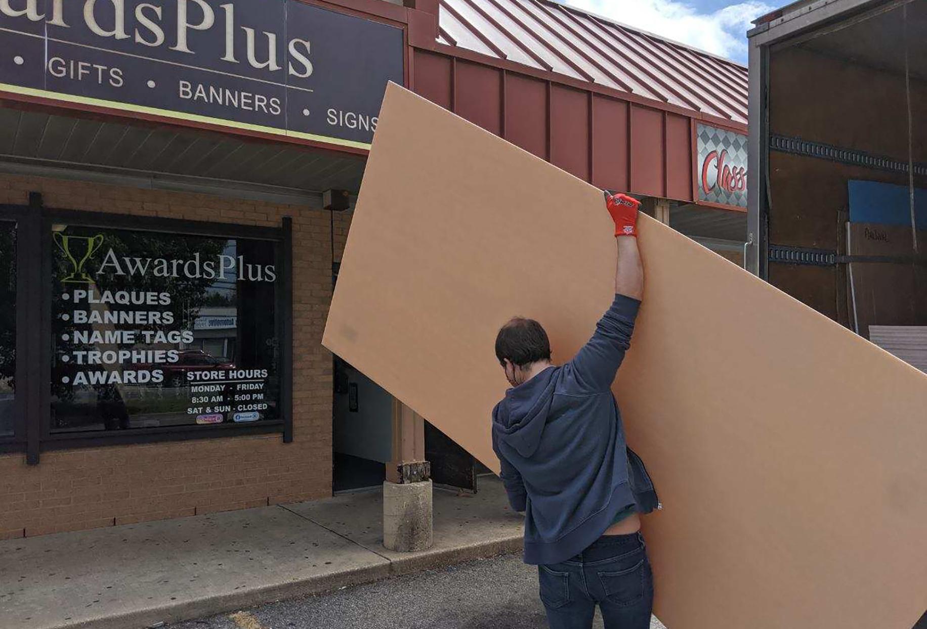 Man carries large acrylic sheet towards building