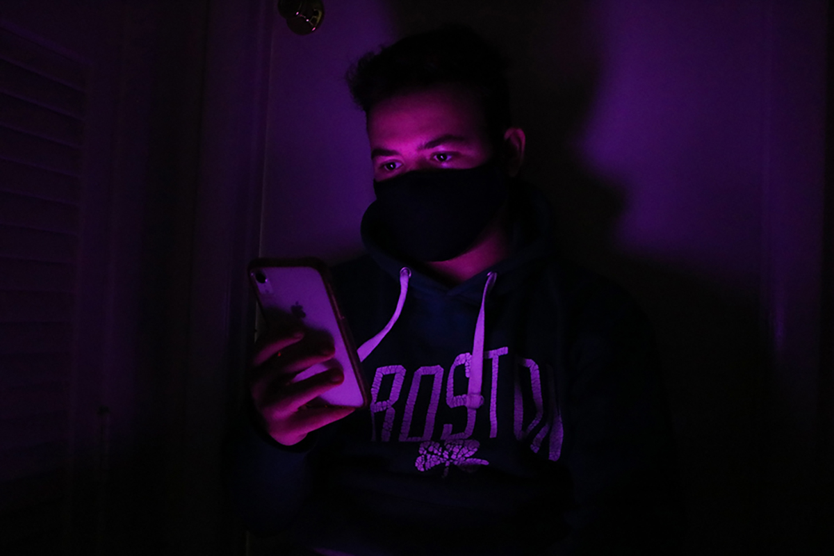 A man on his phone in a purple room