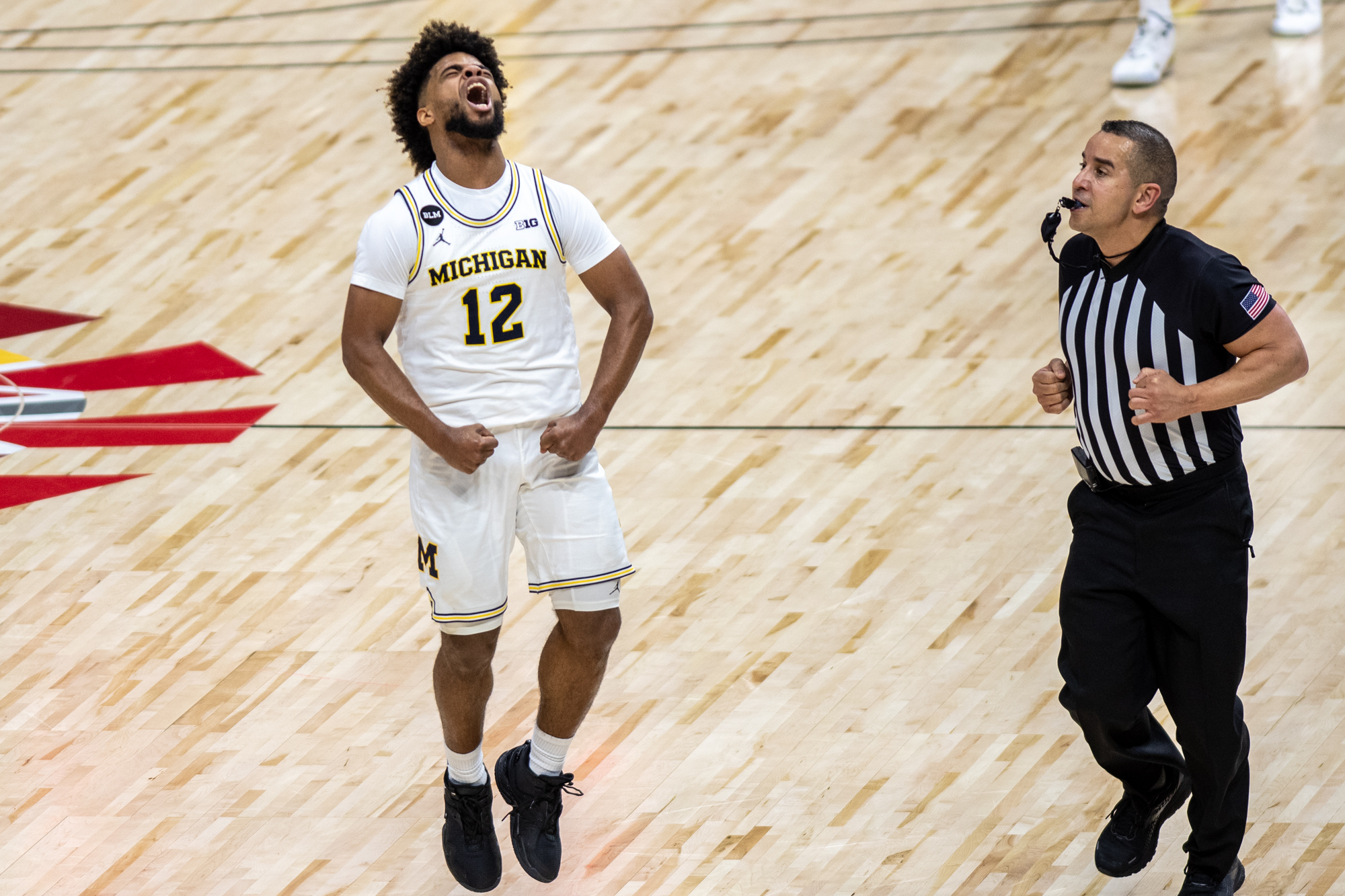 Man in white jersey with maize and blue stripes jumps and screams in excitement while referee watches